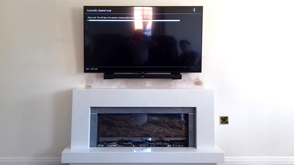 tv hung tidily on wall over modern fireplace